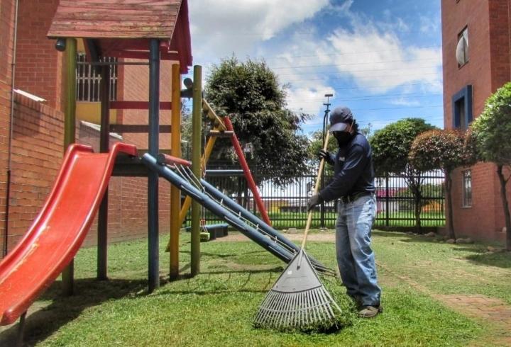 Un trabajador mantiene sus funciones habituales de aseo y mantenimiento al interior del conjunto residencial Portal de San Ángel.