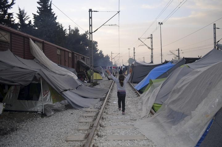 Niñas corren en medio del campo de Idomeni, que estaba compuesto por una antigua estación de tren con antiguos raíles y vagones (2016)
