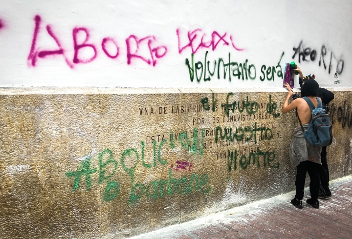 Manifestantes grafitean con stencil en la pared de una iglesia