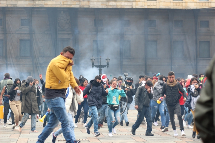 Jóvenes huyen de gases lacrimógenos en la Plaza Simón Bolívar el 22N