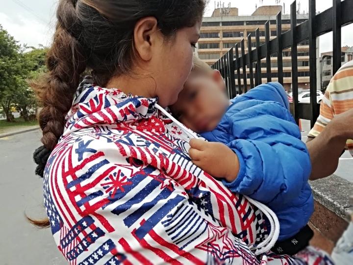 Madre venezolana con su hijo a las afueras del Terminal de Transportes