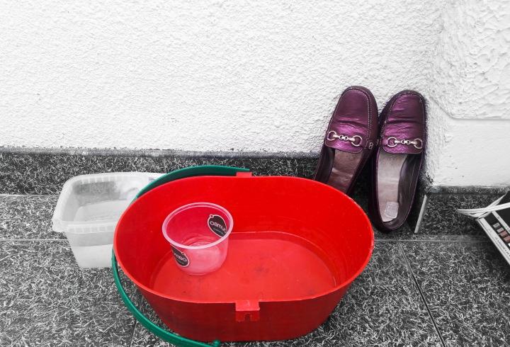 Balde con agua y jabón junto a zapatos que son usados a la hora de salir de casa para evitar la transmisión del virus