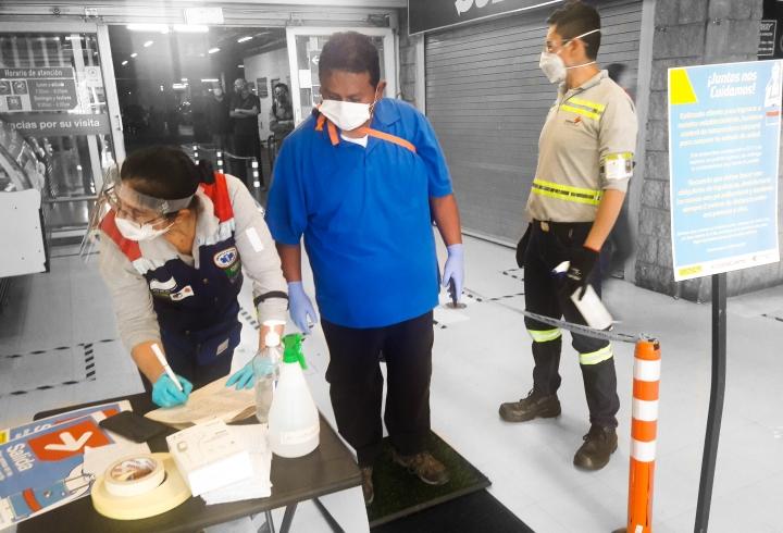 Punto de desinfección de manos y pies en la entrada a Homcenter, en este se rocían a los clientes con alcohol como medida preventiva