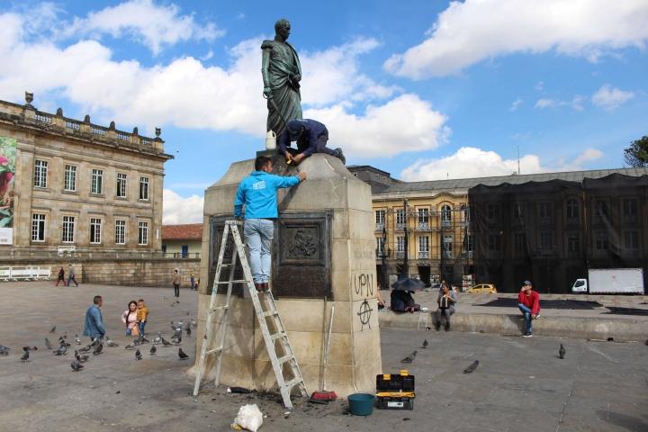 Miembros de la Alcaldía tratando de limpiar el monumento a Simón Bolívar.