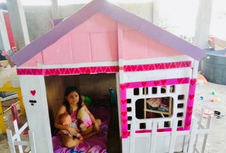 Emily juega en la casa de cartón que les hizo a sus muñecas, en compañía de su madre.