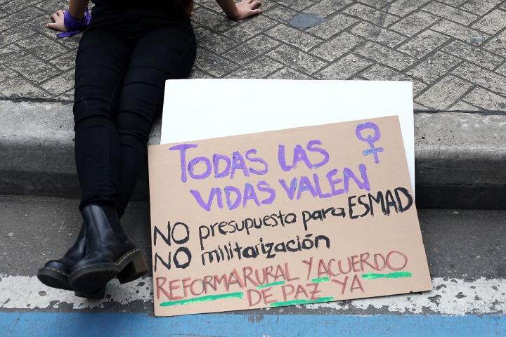 Mujer con pancarta sentada en el suelo