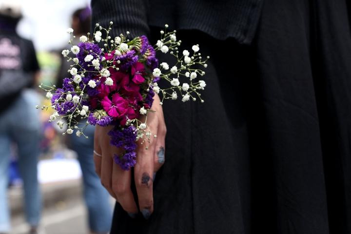 Manifestante con flor en la mano