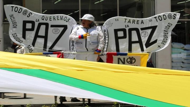 Una de las representaciones simbólicas de la paz en la carrera Séptima y debajo la bandera de la Unión Patriótica.
