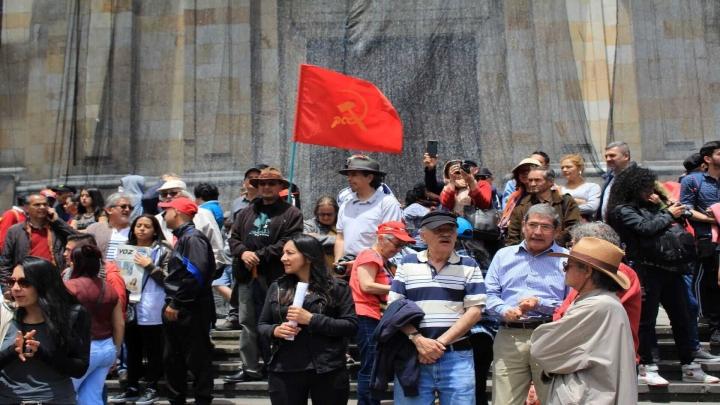 Manifestantes frente a la Catedral Primada con una bandera de la causa comunista