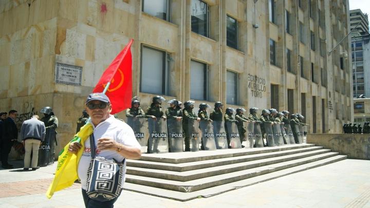 Miembro de Partido Comunista marcha en frente de efectivos de la Policía