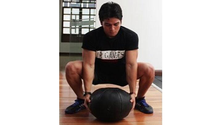 Entrenamiento funcional: sentadilla con balón medicinal.