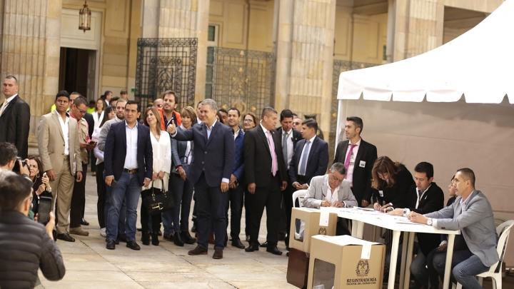 El candidato por el Centro Democrático, Iván Duque, saluda a la prensa al acompañar a Álvaro Uribe en el Congreso. Crédito: Fátima Martínez
