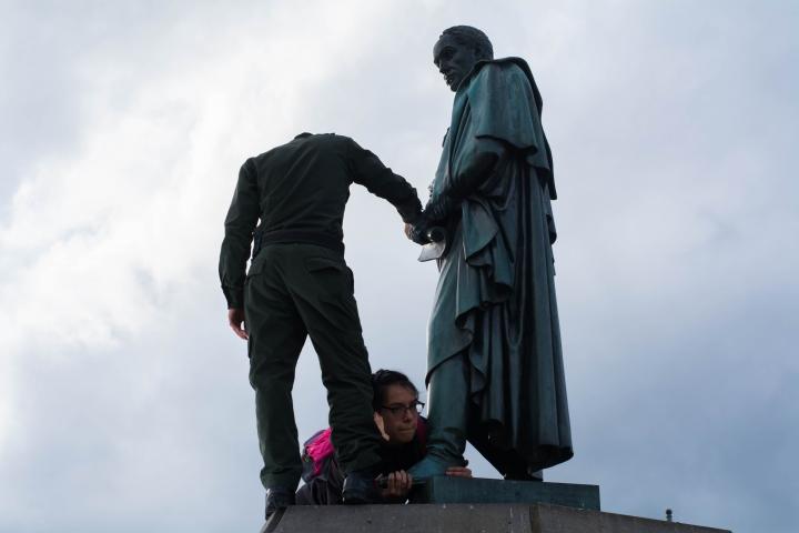 """Aferrada al pie de la estatua desvestida, la mujer que intentó convertir a Simón en """"Simona"""" hace resistencia. Foto: Julián Ríos"""