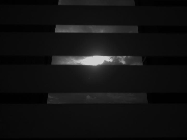 """""""El otro lado"""". El cielo se ve desde las ventanas de las casas, se vive desde una perspectiva muy oscura, sin poder salir. Se restringe el otro lado de la ventana."""