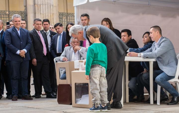 El expresidente y senador Álvaro Uribe Vélez votando en compañía de su nieto. Foto: Julián Ríos